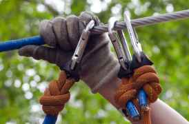 person in gray and beige gloves holding on gray cable wire